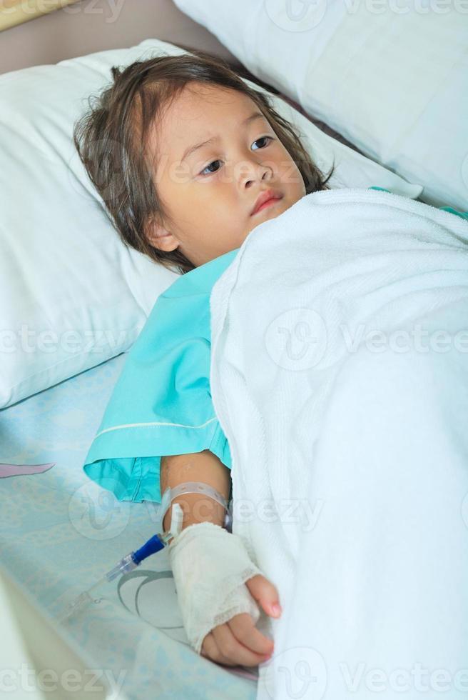 menina doente na cama do hospital foto