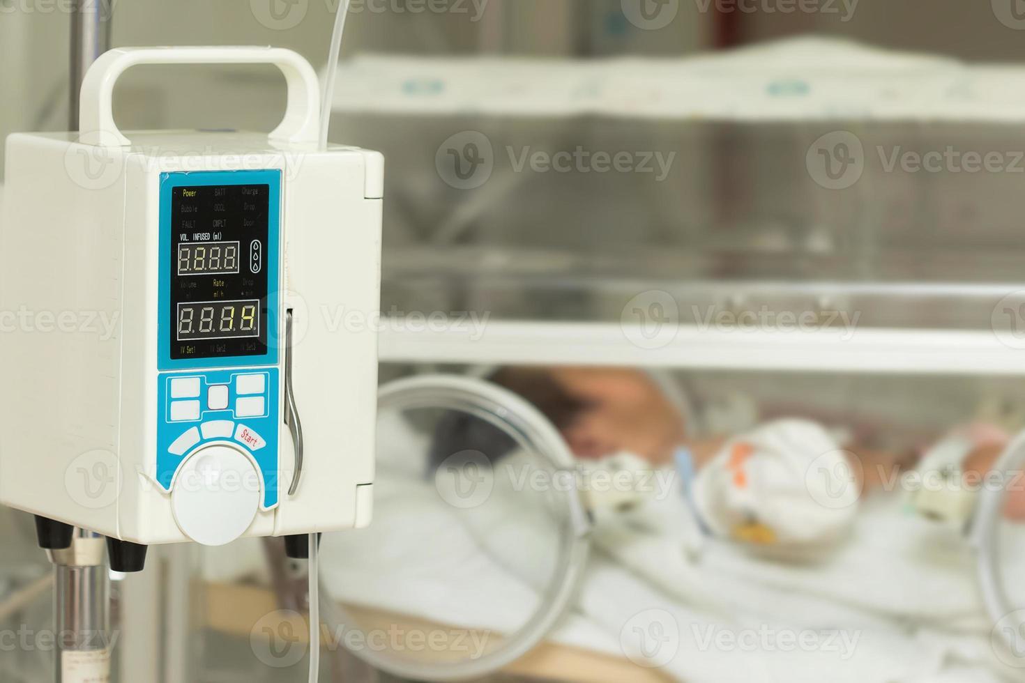 bomba de infusão que alimenta gotejamento iv em pacientes do bebê foto
