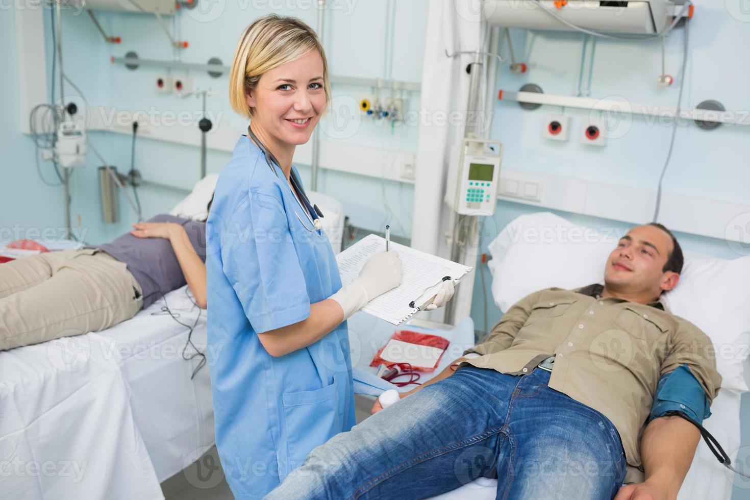enfermeira olhando para a câmera ao lado de pacientes transfundidos foto