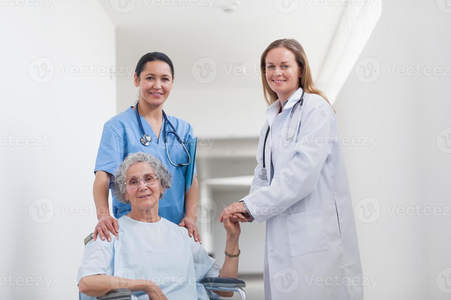 paciente no corredor, segurando a mão de um médico foto