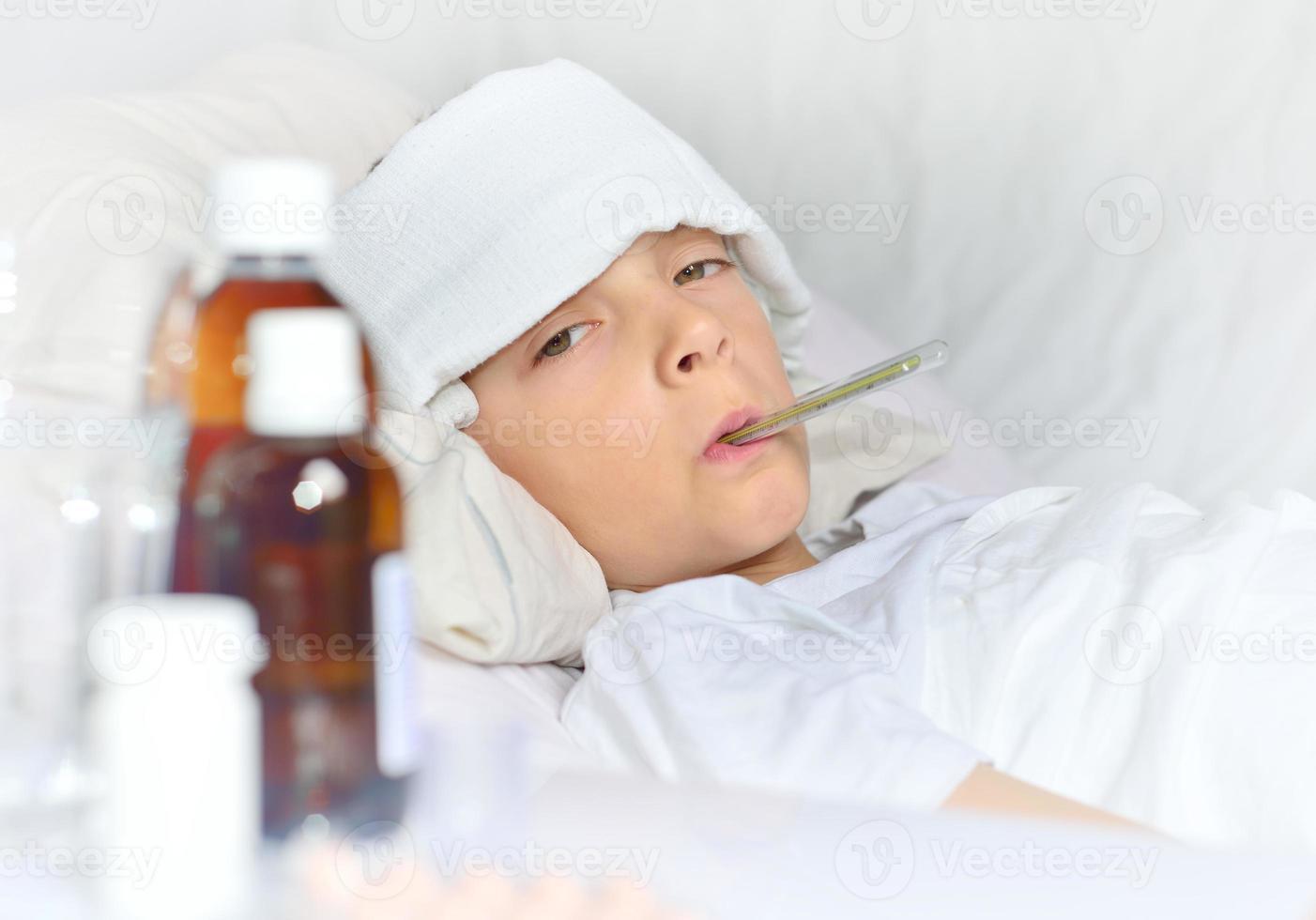 menino doente, deitado na cama foto