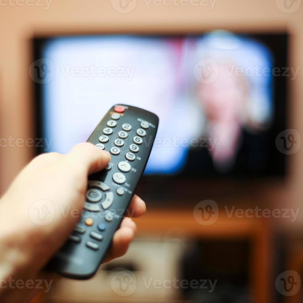 assistindo tv e usando o controle remoto foto