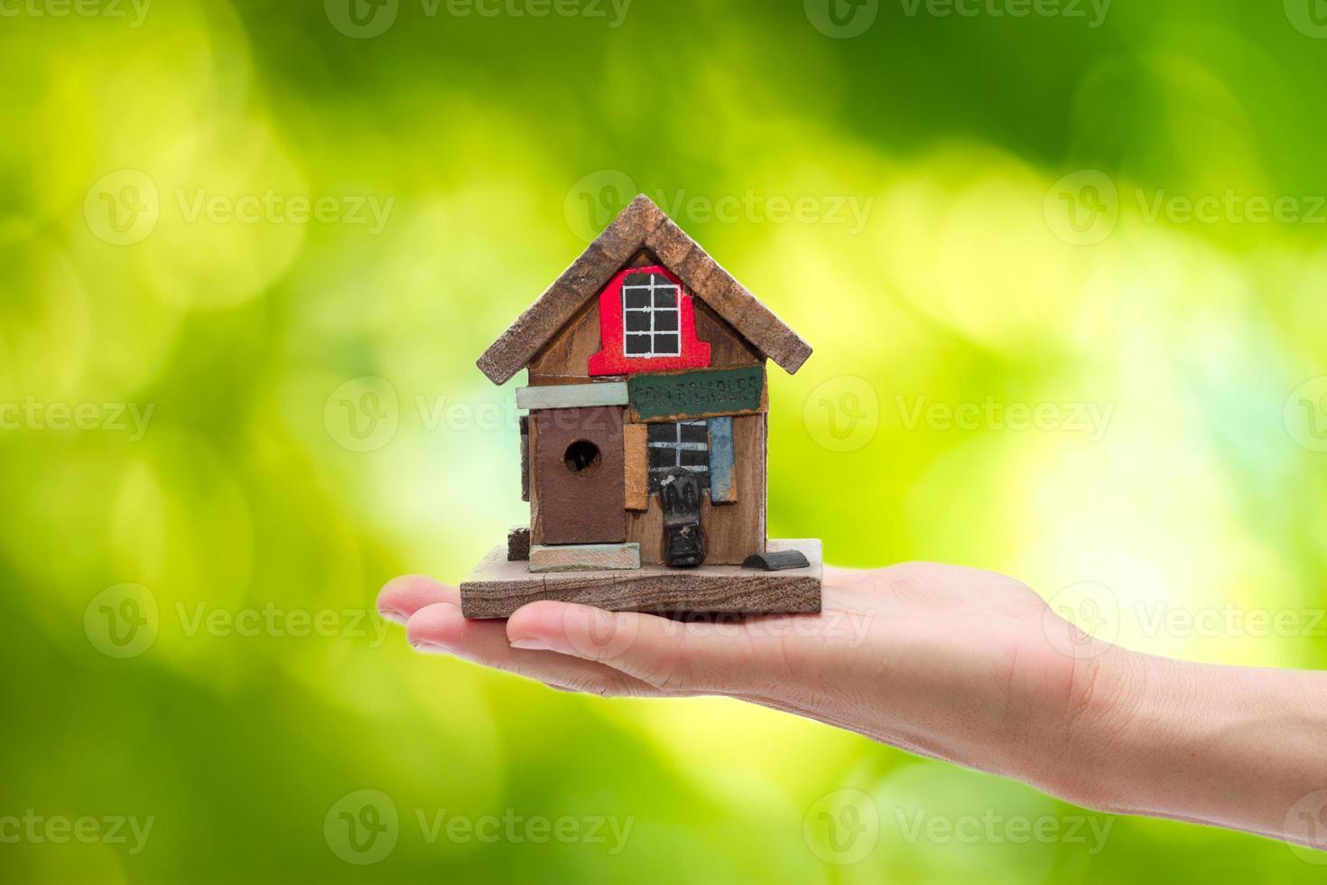 fechar-se. mão do homem segurando a casa isolada no fundo branco foto