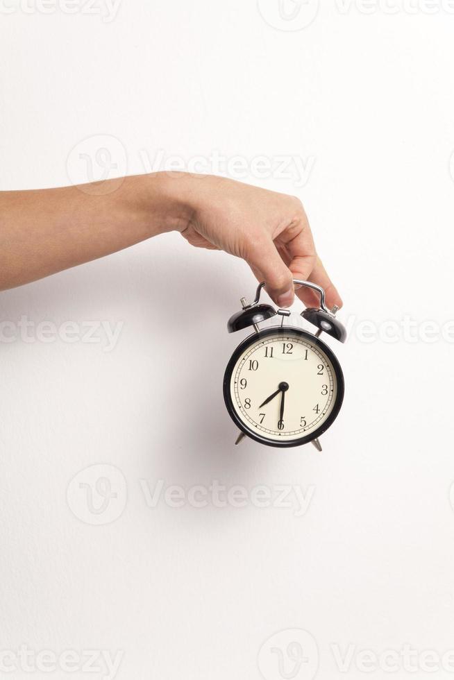 mão segurando um despertador no fundo branco foto