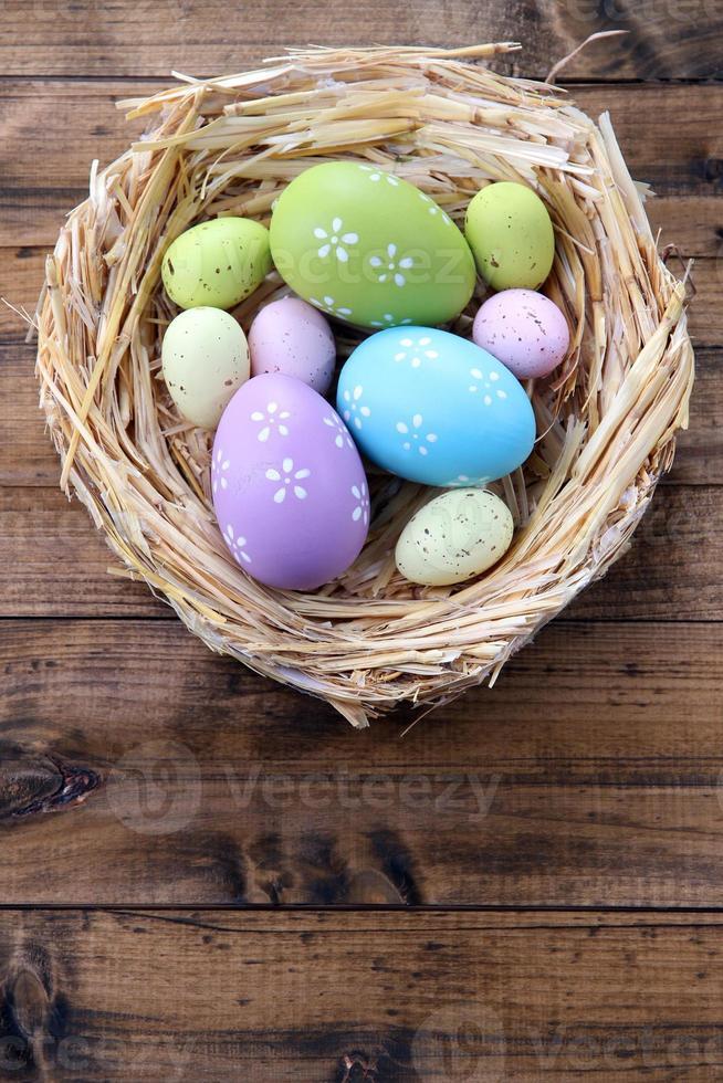 ovos de Páscoa no ninho na cor de fundo de madeira foto