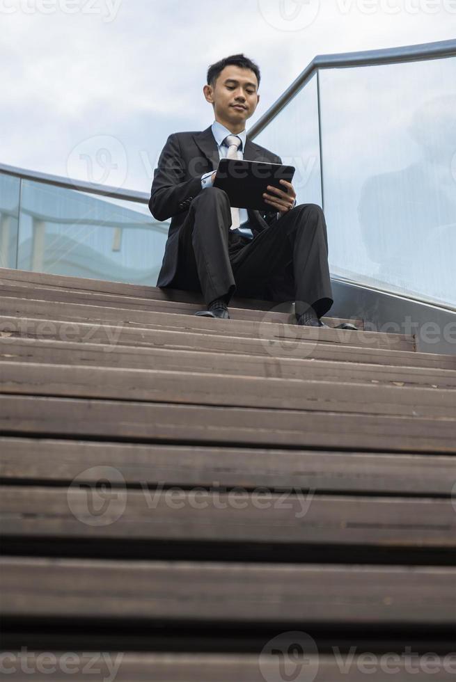 homem de negócios asiáticos usando computador portátil no parque da cidade foto