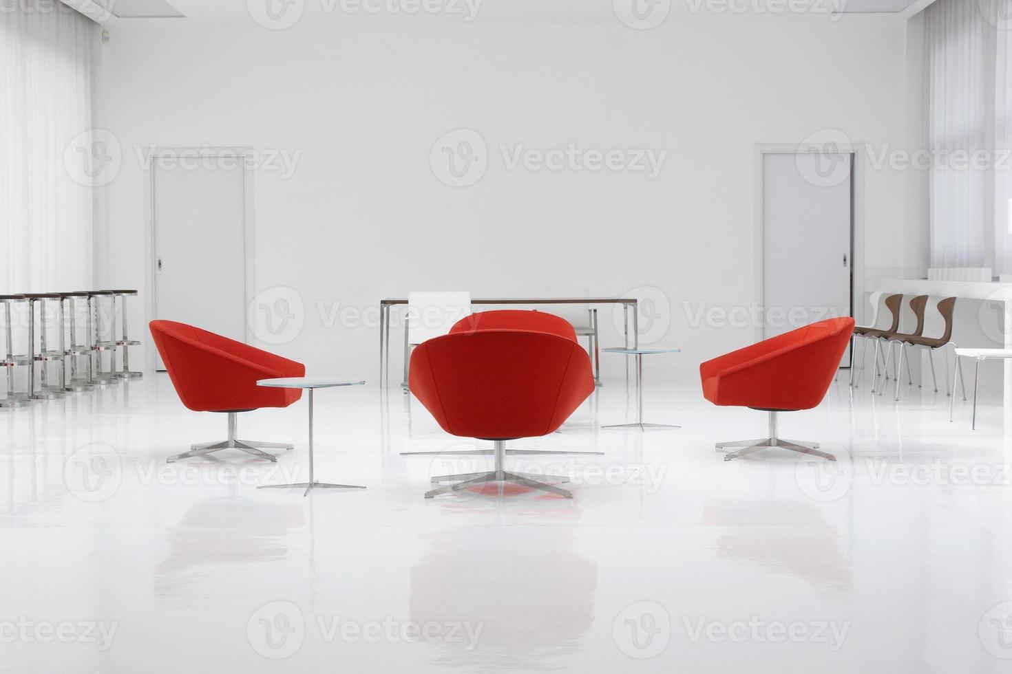 um loft moderno com cadeiras vermelhas e paredes brancas foto