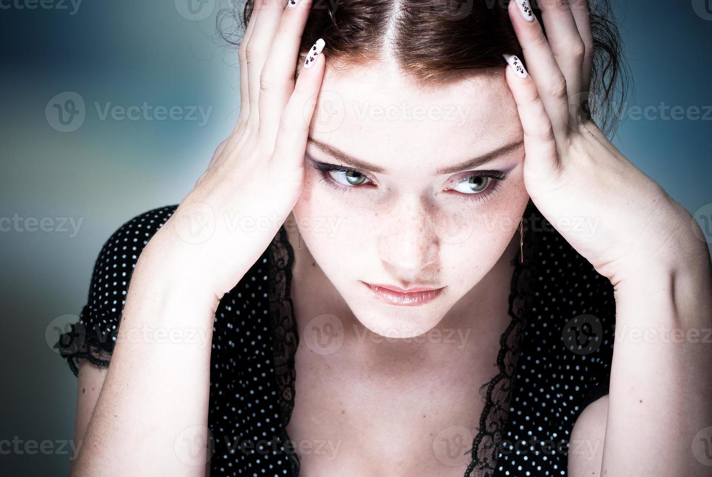 jovem, concentrando-se com a cabeça nas mãos foto