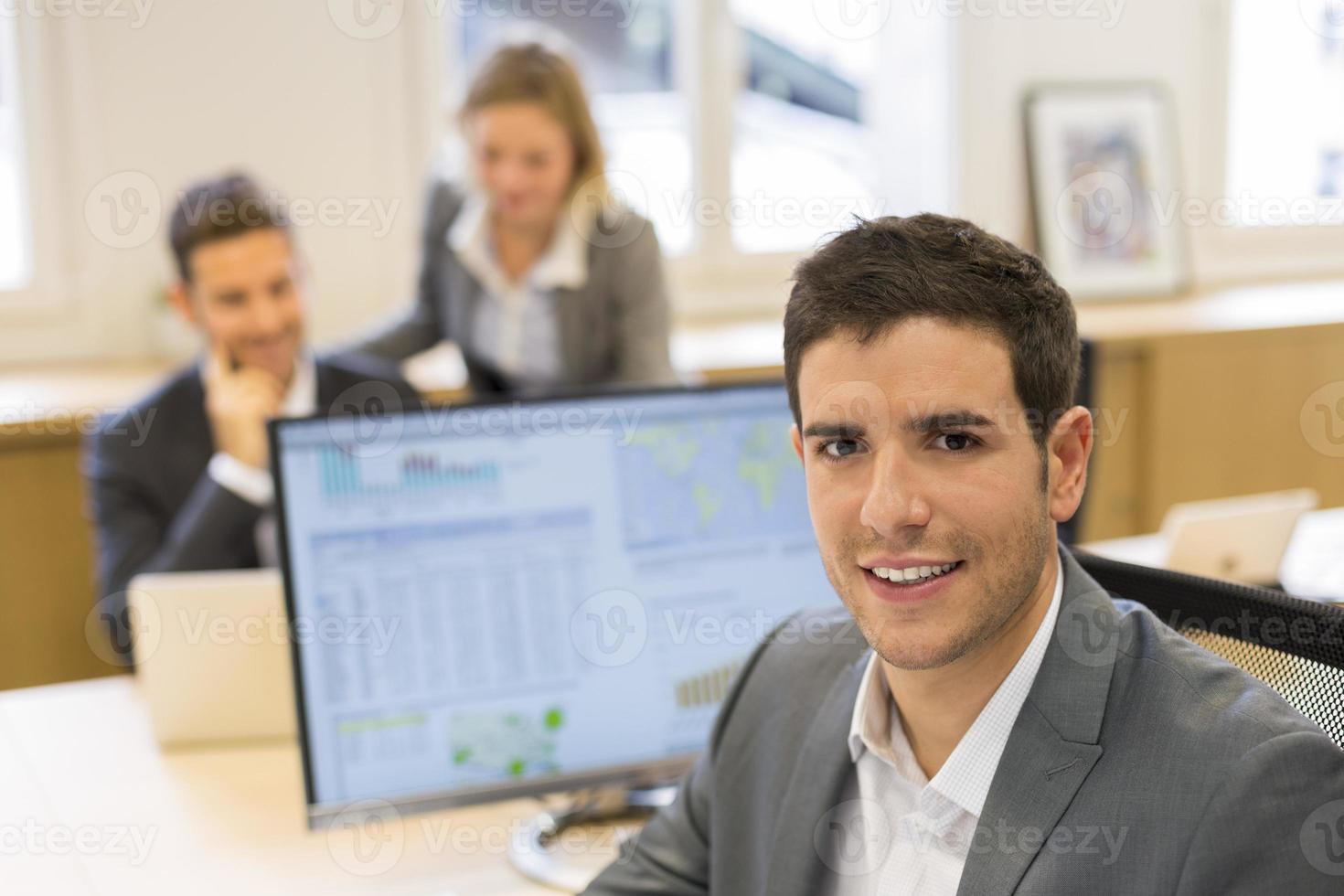 retrato do empresário bonitão no escritório moderno. olhando câmera foto