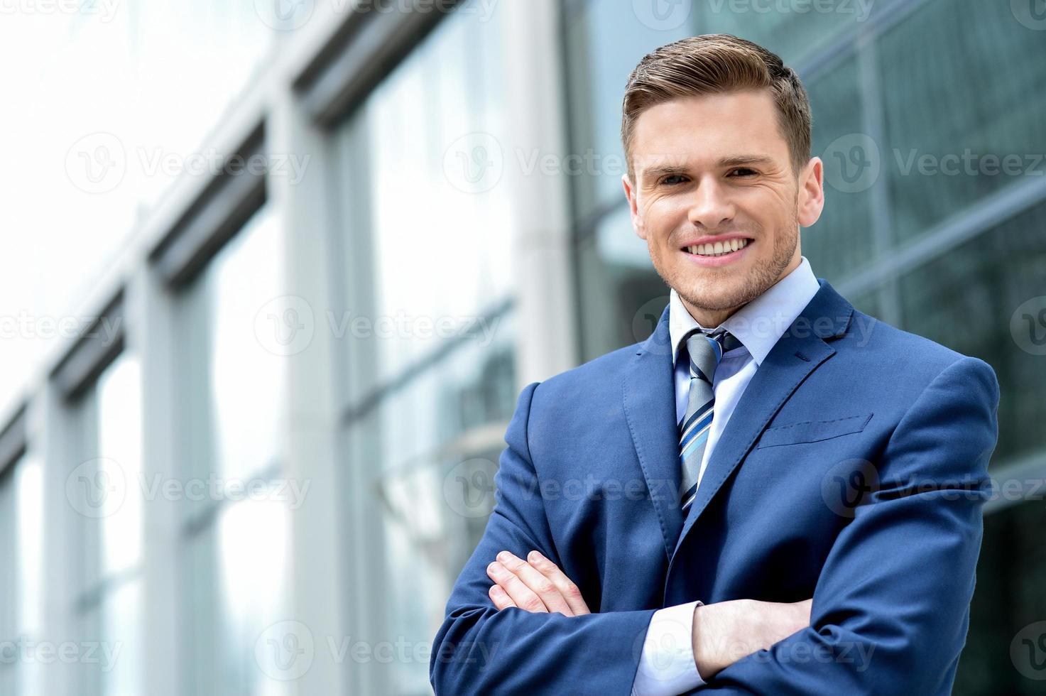 jovem empresário sorrindo em um escritório ao ar livre foto