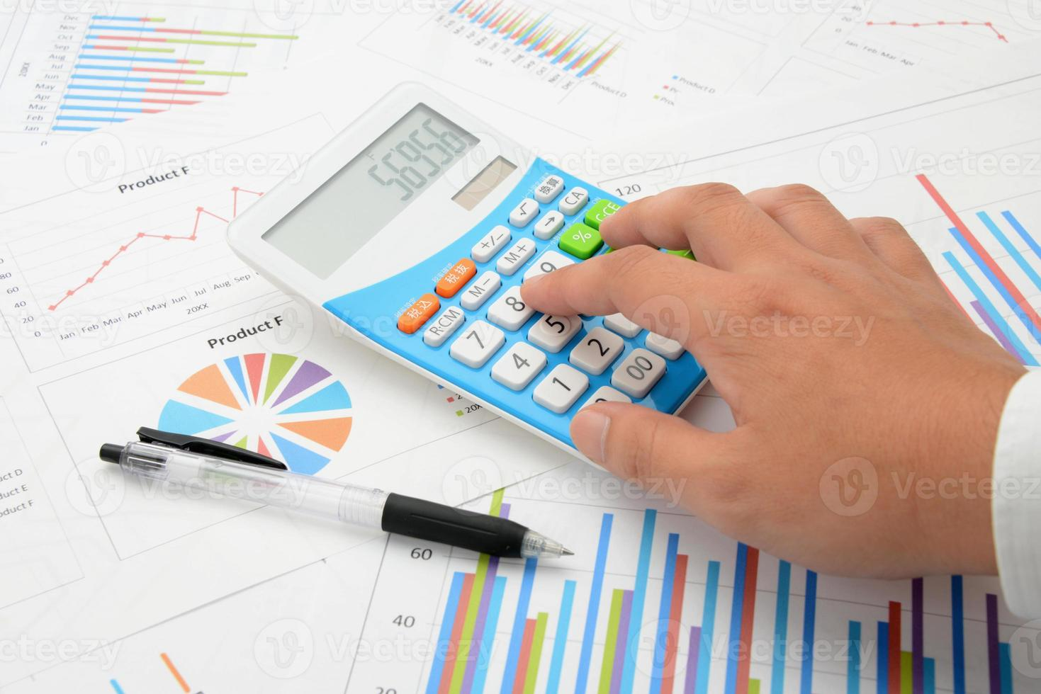 mão do empresário usando calculadora foto