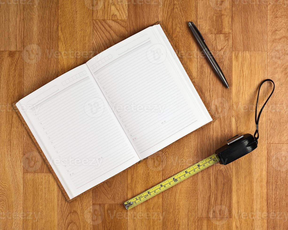 bloco de notas em branco com material de escritório, mesa de madeira. foto