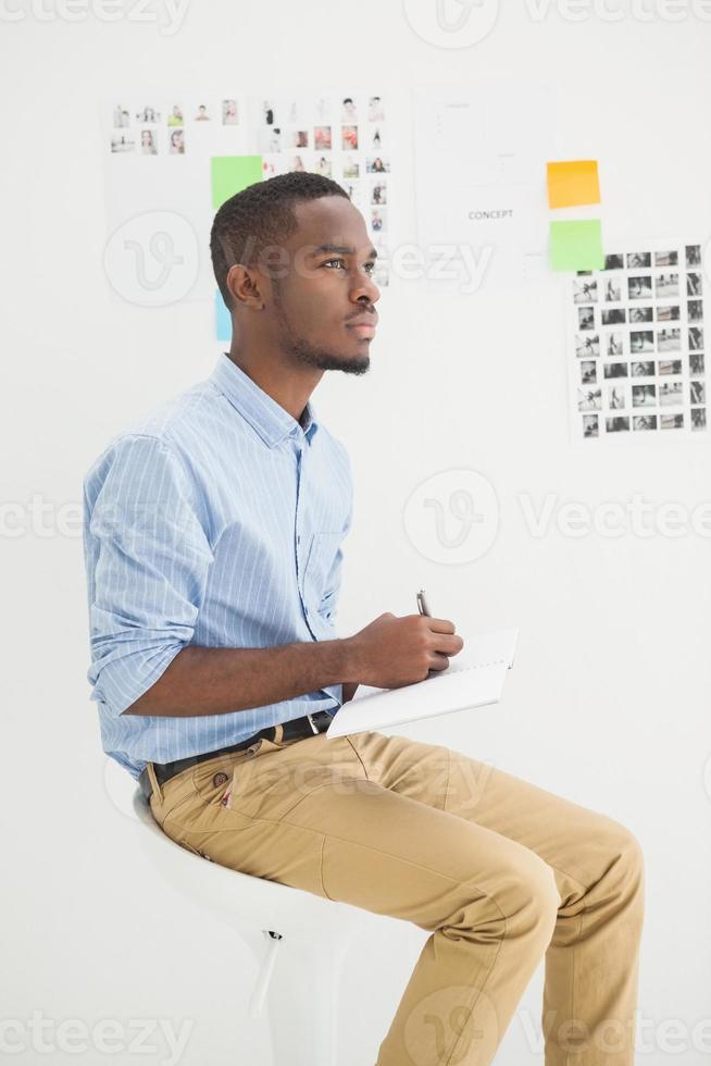 empresário pensativo sentado escrevendo no caderno foto