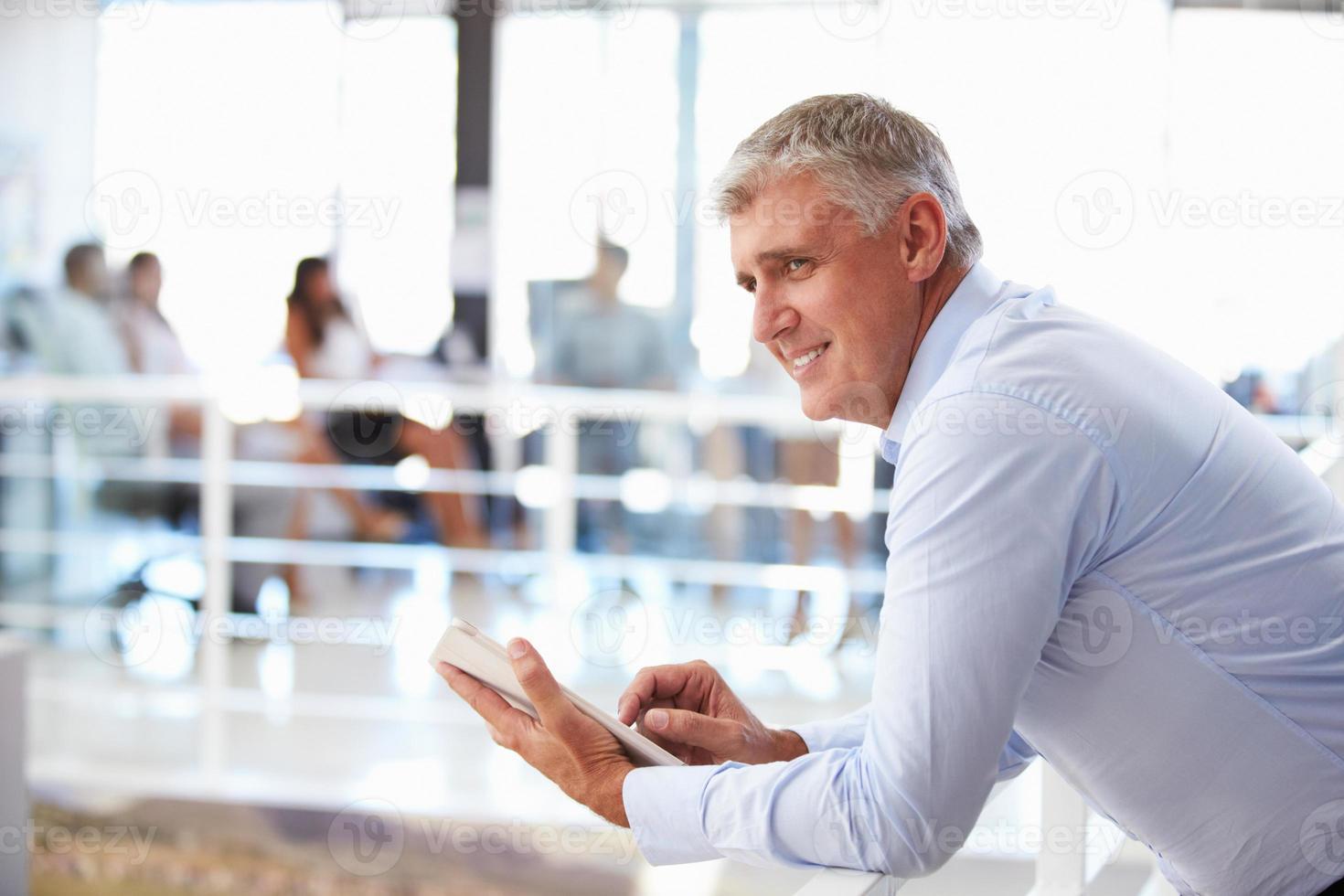 retrato de homem de meia idade no escritório usando tablet foto