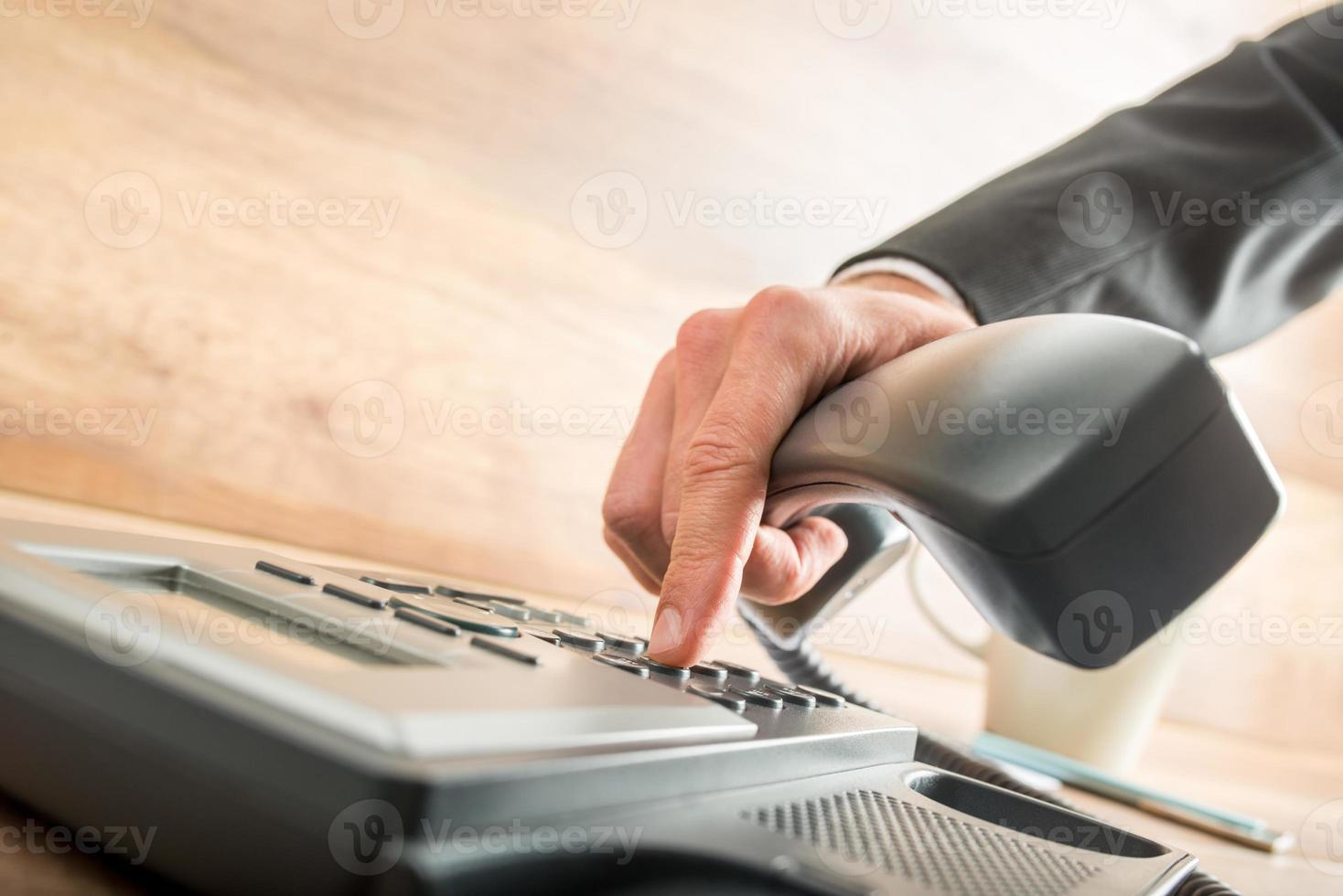 consultor segurando o receptor de um telefone de mesa enquanto disca foto