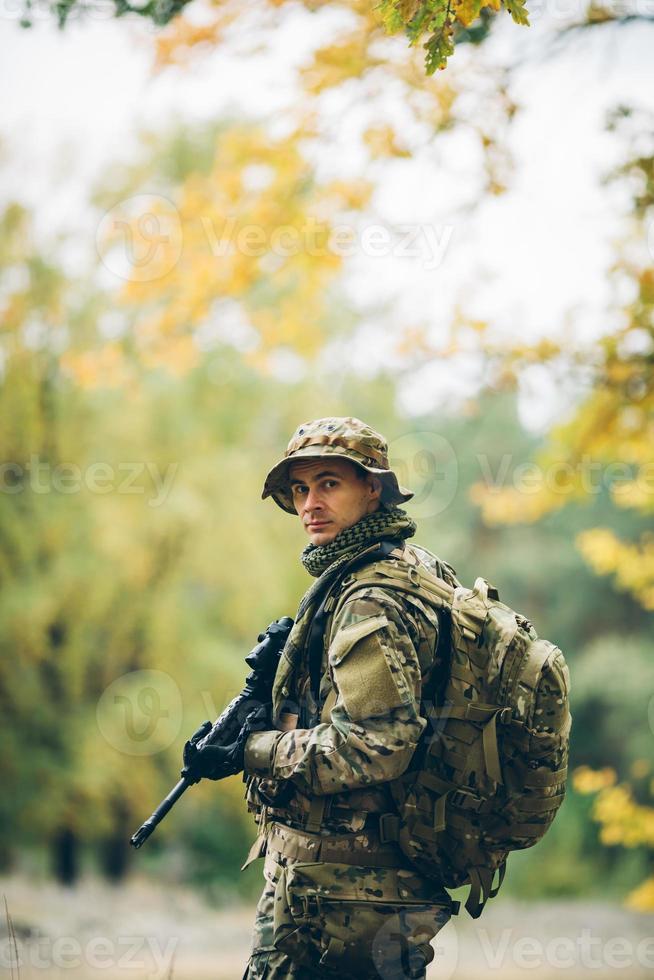 soldado com rifle na floresta foto