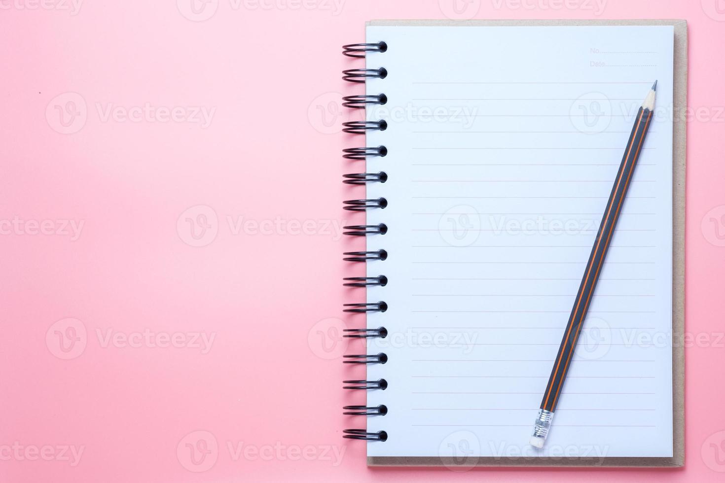 caderno e lápis em fundo rosa foto