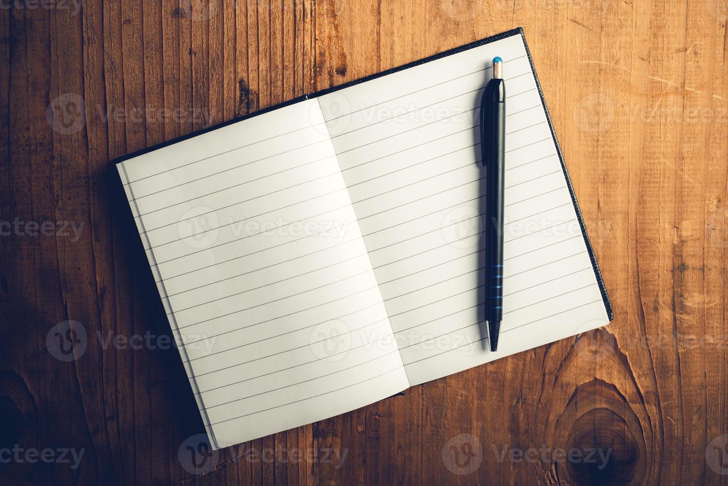 caderno aberto com páginas em branco e lápis foto