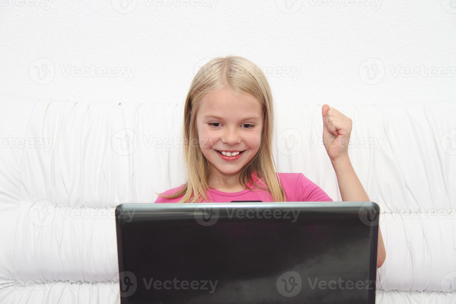 menina com seu laptop em casa foto