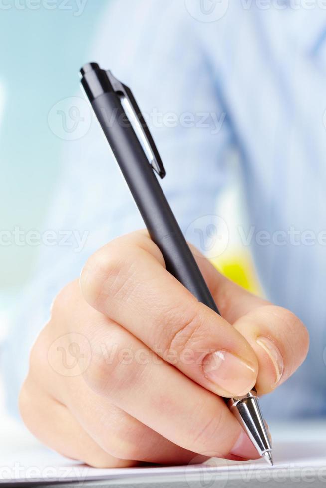 mão com caneta foto