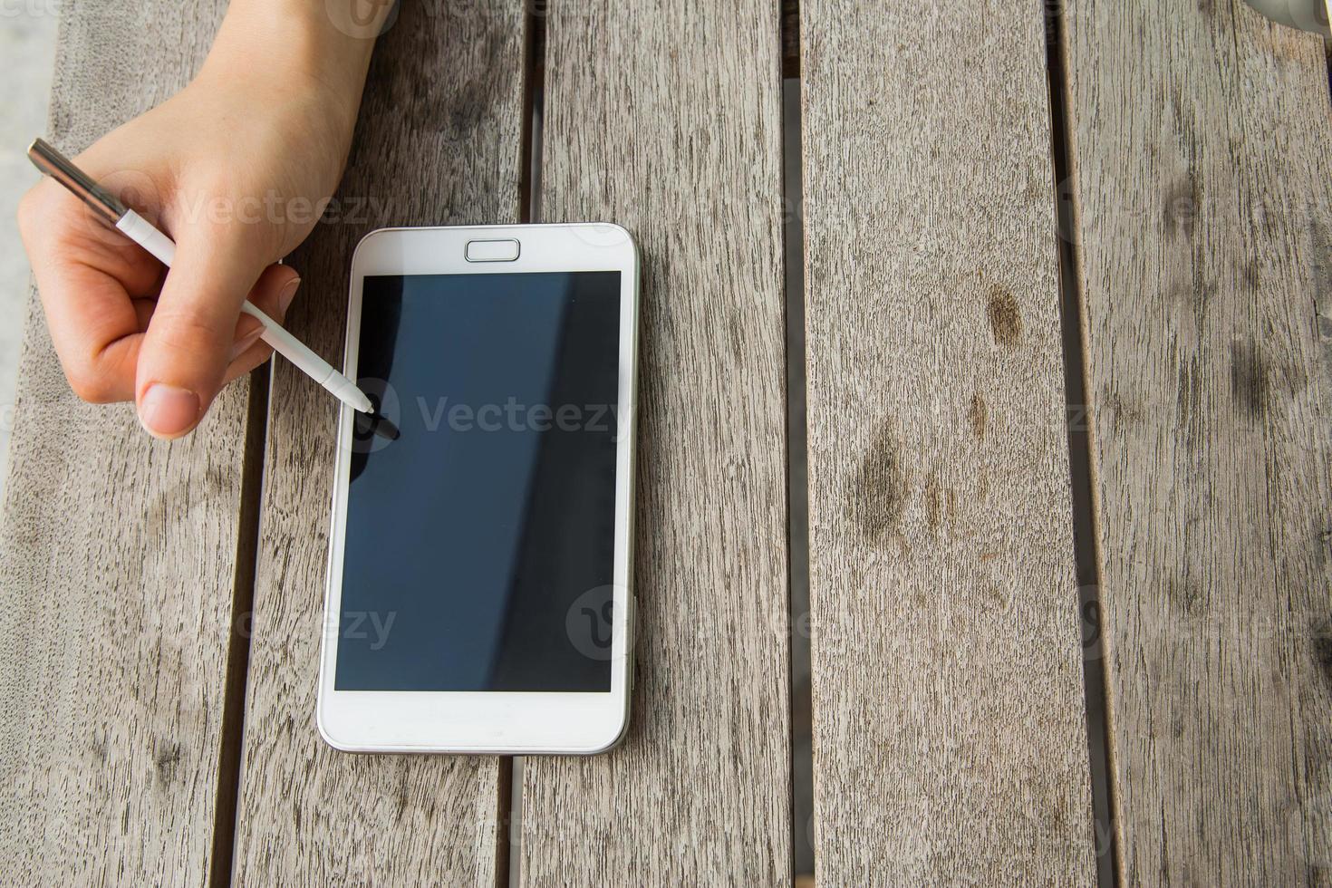 usando telefone inteligente ao ar livre com caneta foto