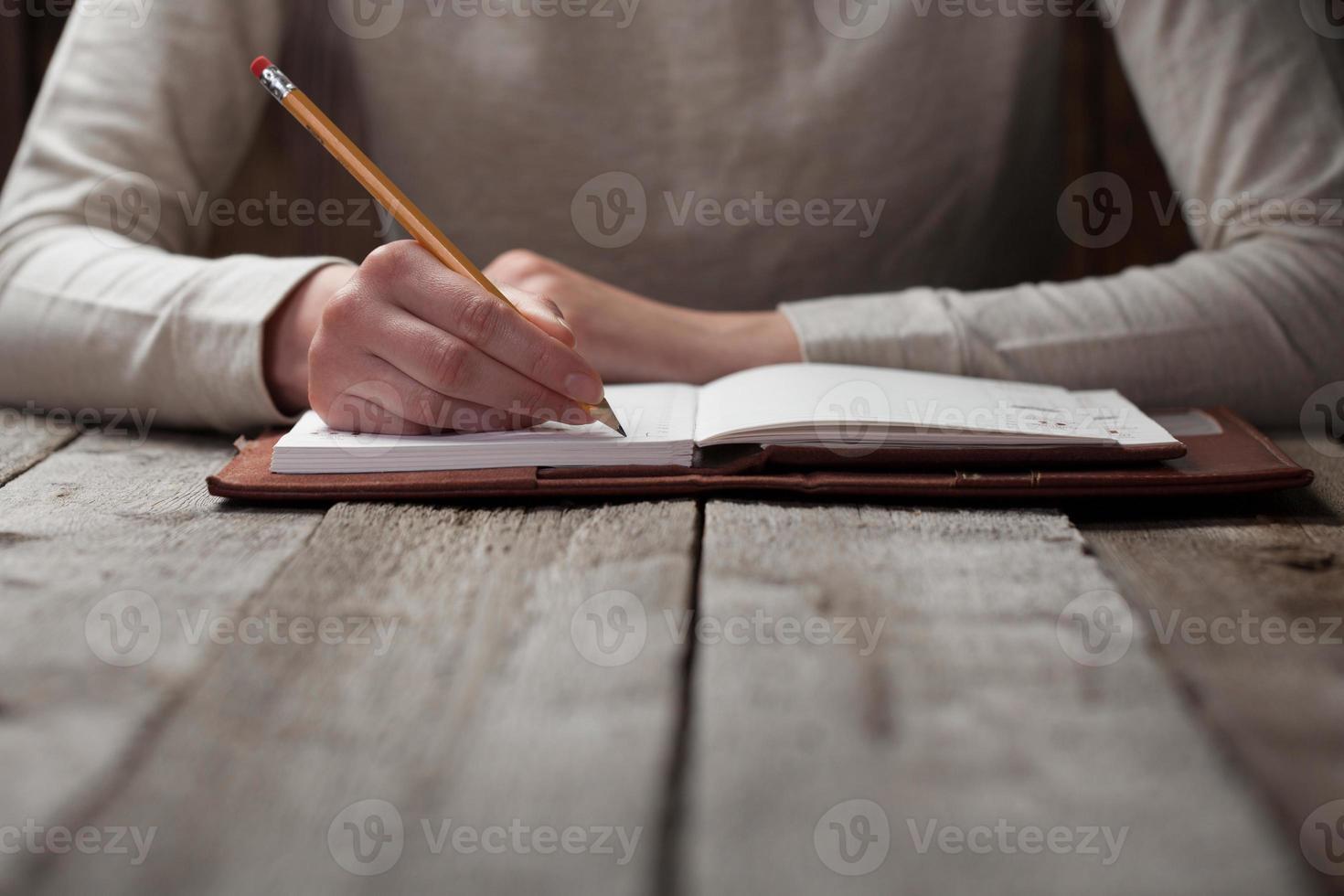 mão escrevendo com uma caneta em um caderno foto