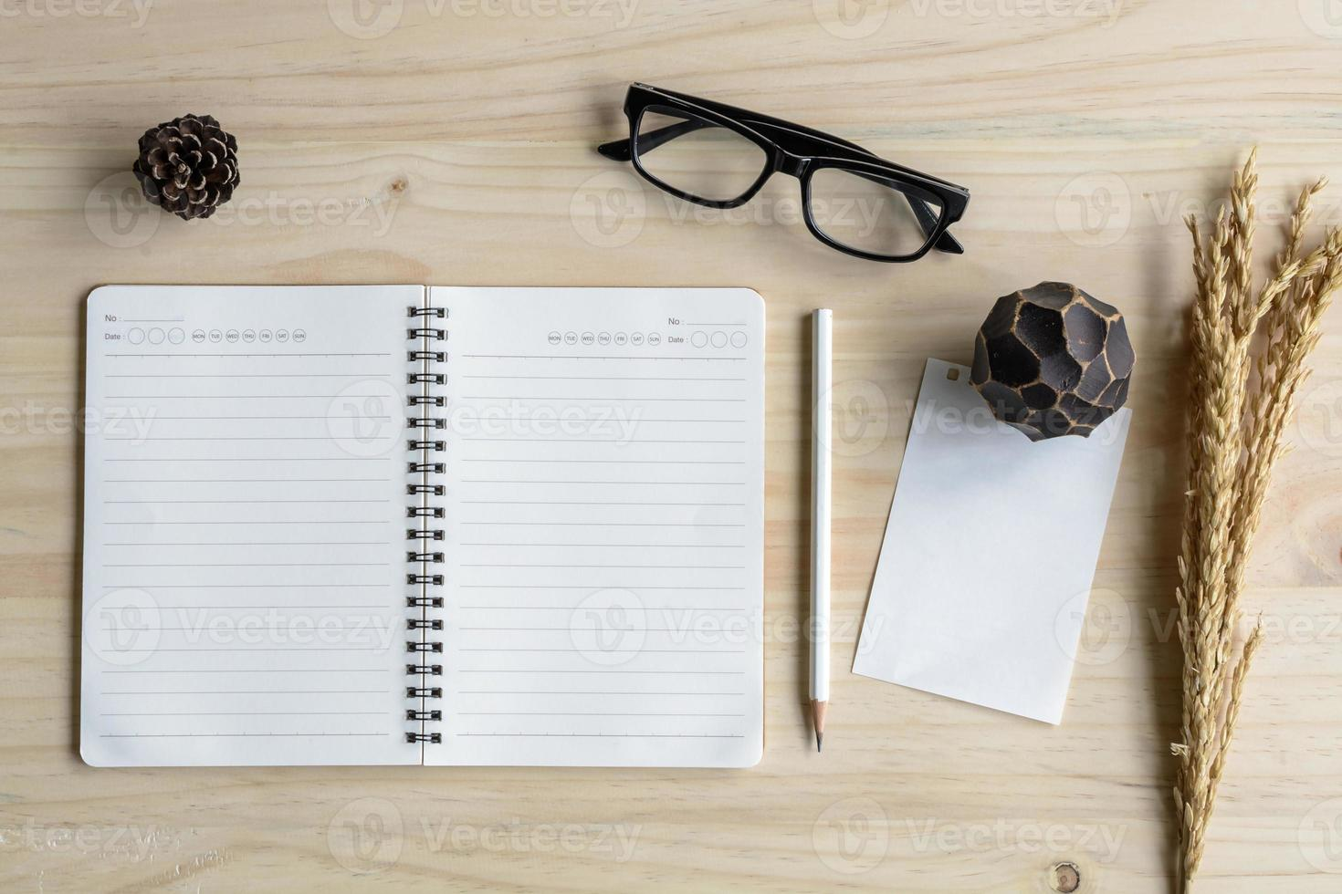 caderno em branco com óculos na mesa de madeira foto