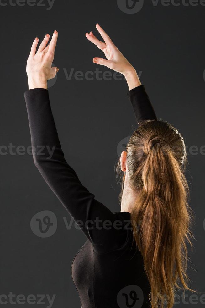 bailarina posando com as mãos em um fundo escuro foto