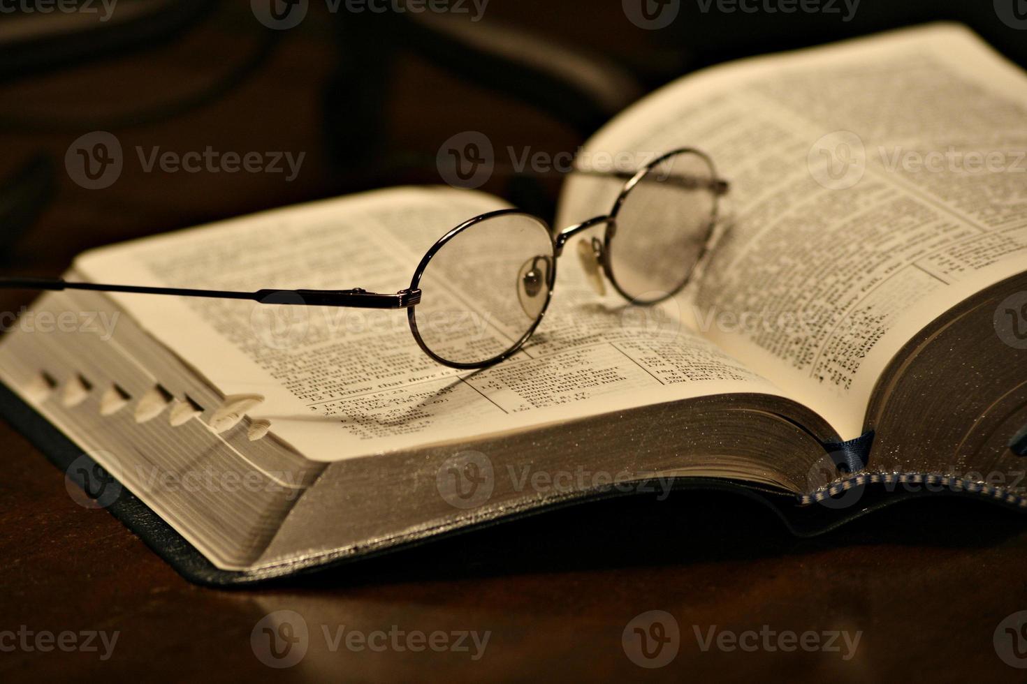 óculos descansando em uma página de um livro aberto foto