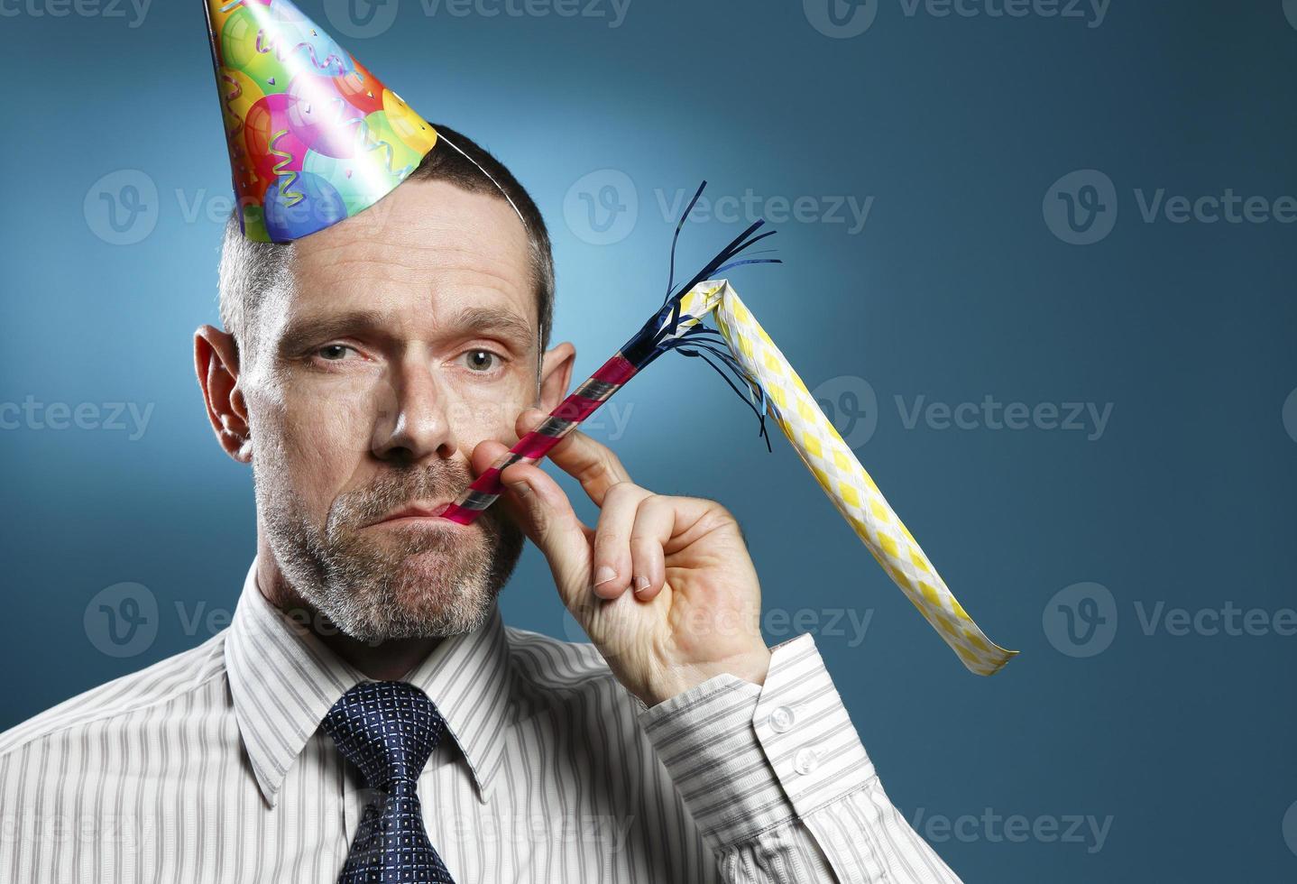homem vestindo gravata com chapéu de festa e soprador de chifre foto