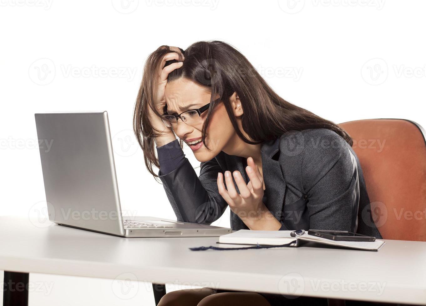empresária jovem chocada olhando em seu laptop foto
