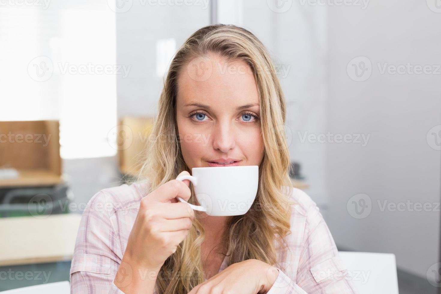 empresária, segurando a caneca de café e sorrindo foto