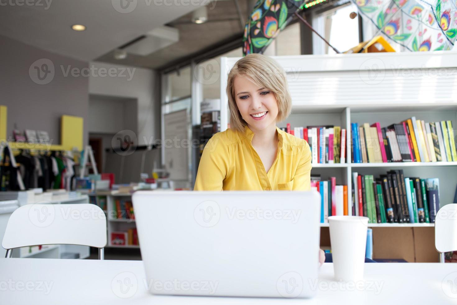 gerente mulher trabalhando no laptop na livraria foto