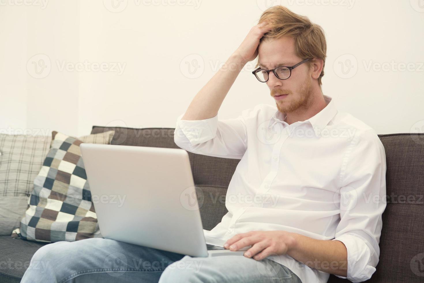 jovem sentado no sofá com o laptop foto