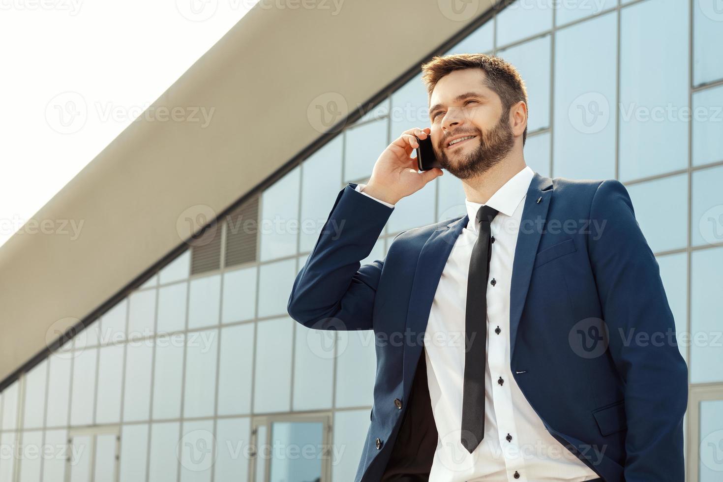 jovem empresário falando ao telefone ao ar livre foto