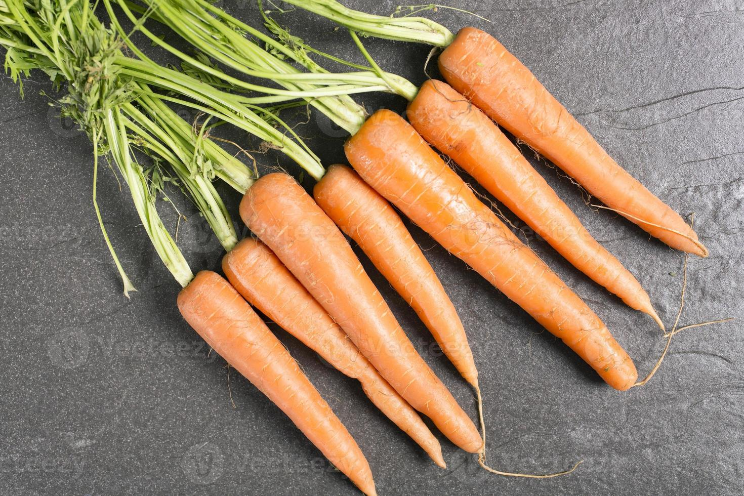 cenouras frescas na ardósia preta foto