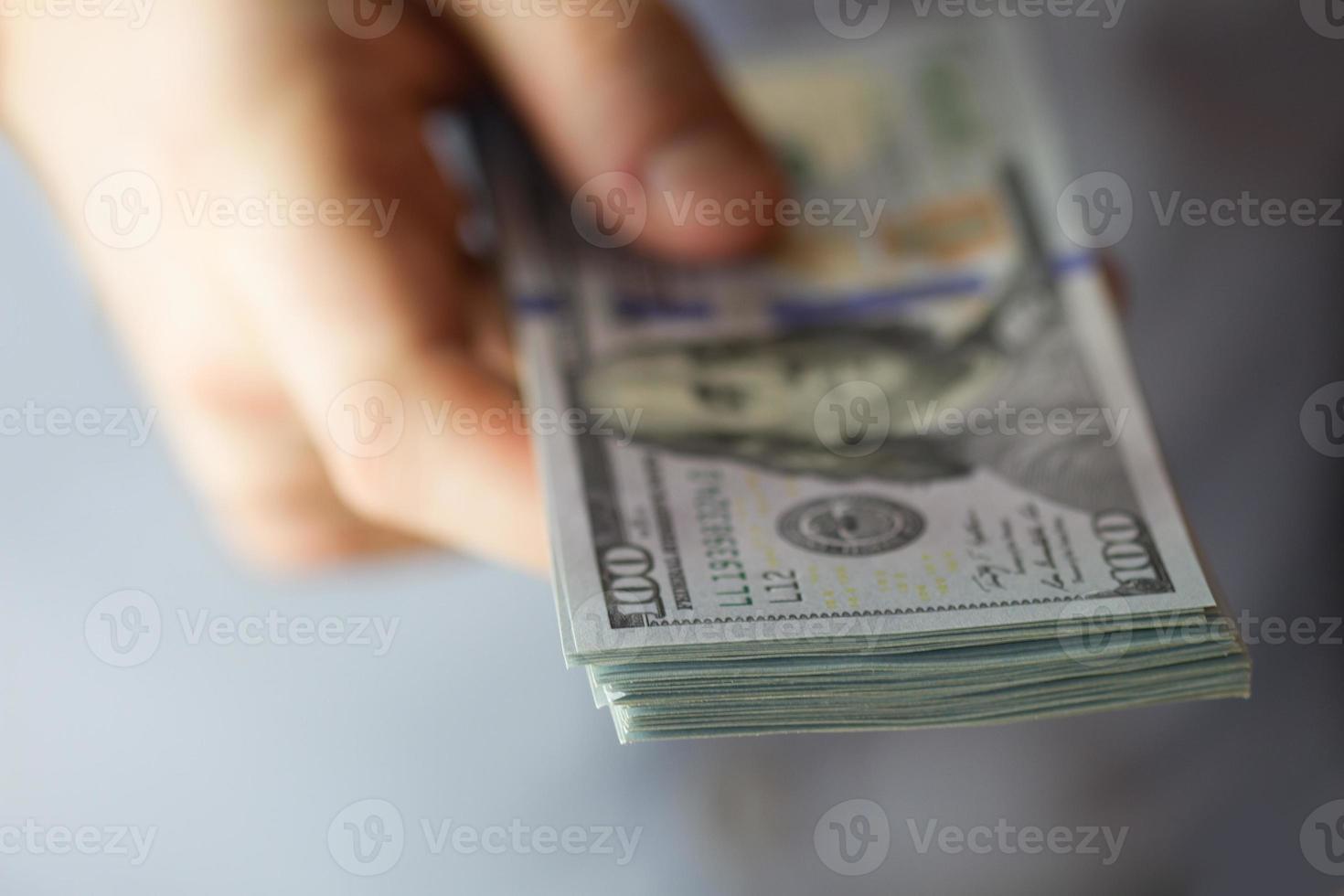 pilhas de cem dólares na mão foto