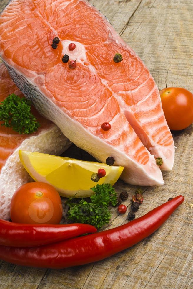 salmão cru, legumes e especiarias em uma mesa de madeira velha foto