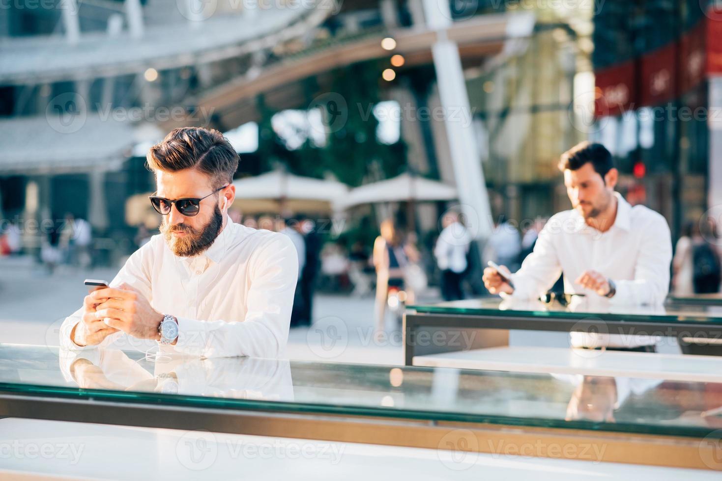 dois empresário bonitão usando smartphone foto