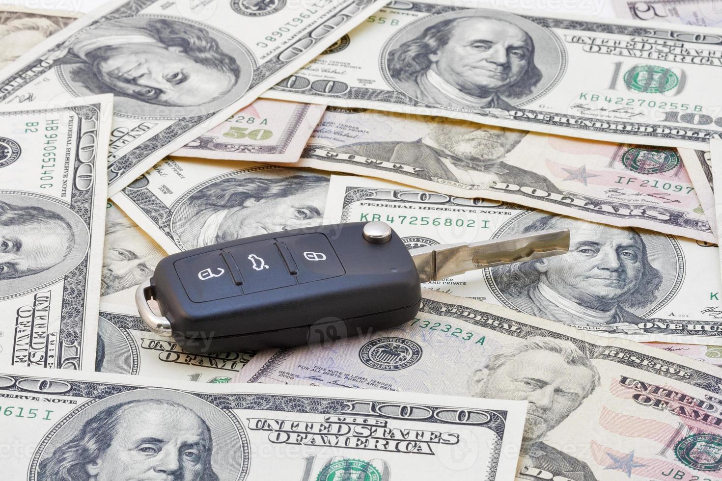 chaves do carro sobre as notas de dólar foto