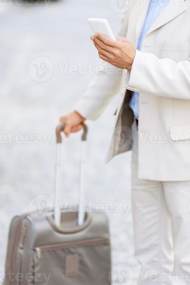 homem hansome segurando sua mala de viagem foto