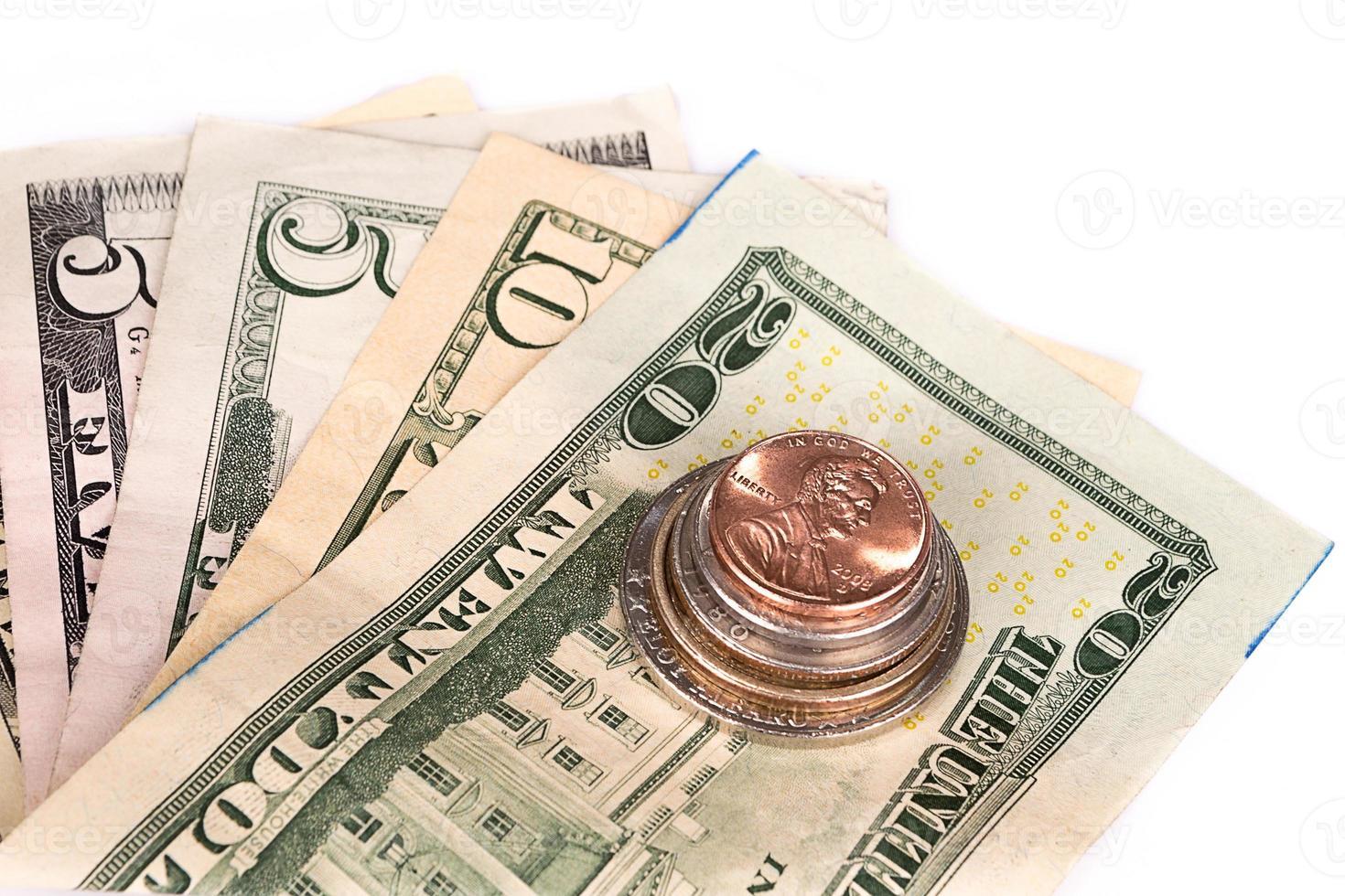 várias pilhas de moedas americanas com algumas notas de dólar. foto