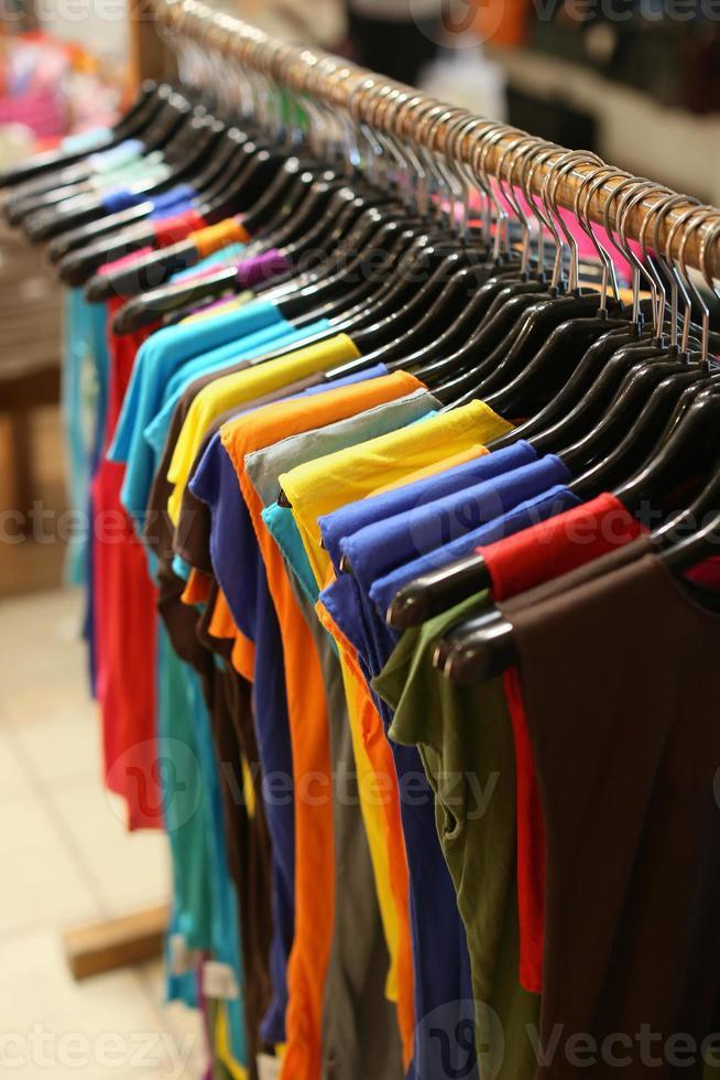 rack de camisas coloridas penduradas à venda em uma feira foto