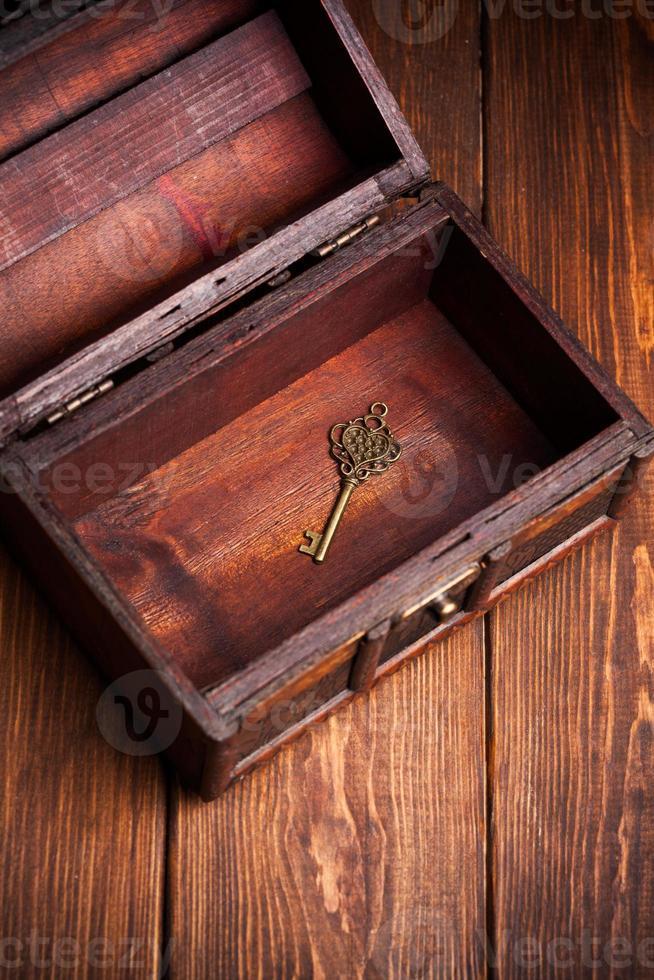 chave vintage dentro da velha arca do tesouro em fundo de madeira foto