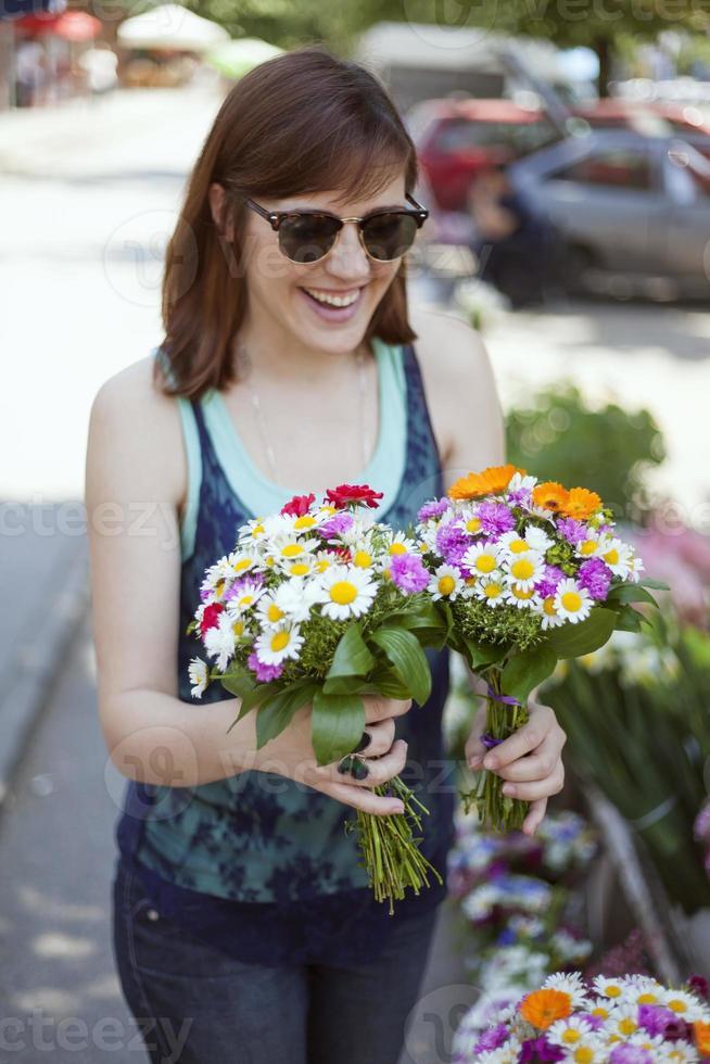 jovem mulher na loja de florista foto