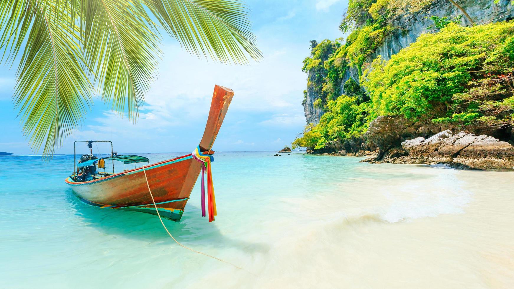 barco de conto longo na praia branca em phuket, Tailândia foto