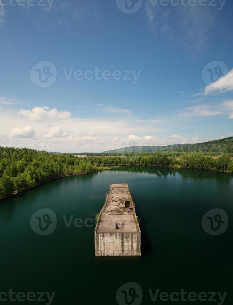 estrutura de concreto industrial como ilha no rio bonito na natureza foto