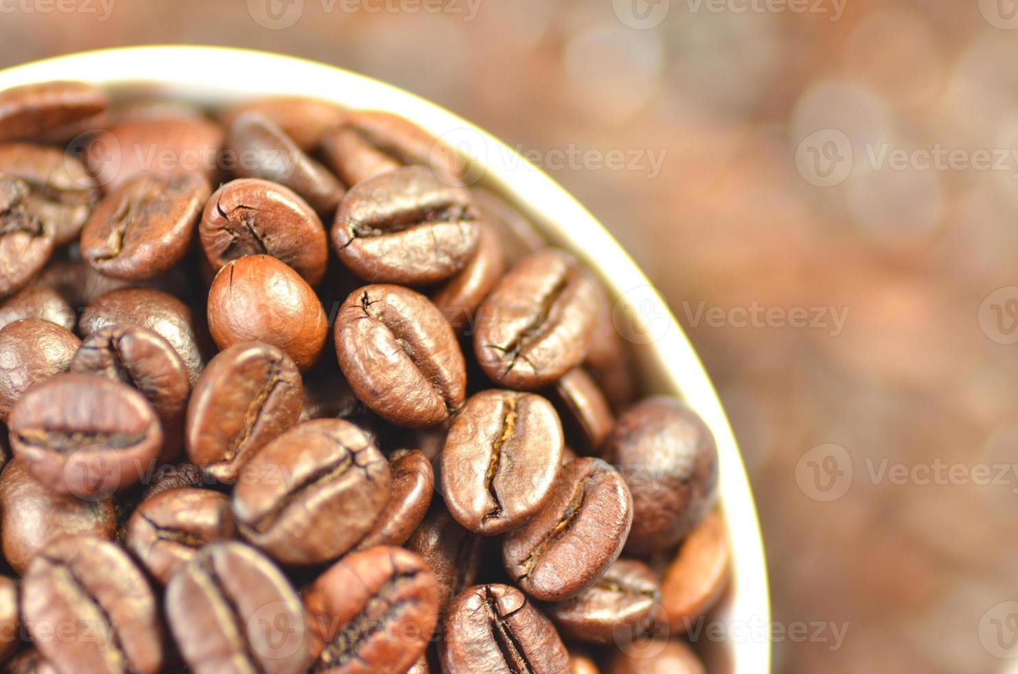 xícara de café branca cheia de grãos de café foto