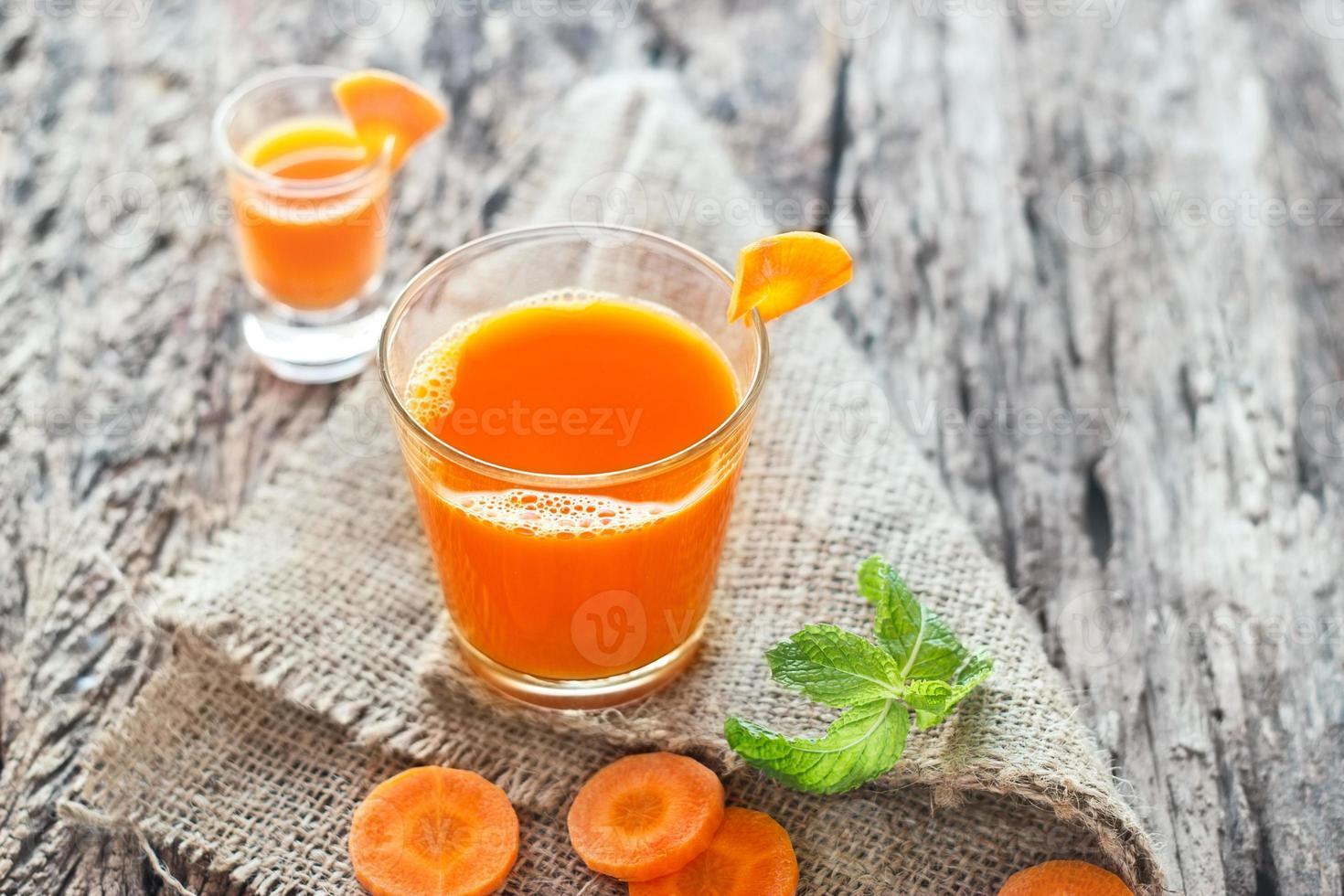 suco de cenoura fresca no saco e fundo de madeira foto