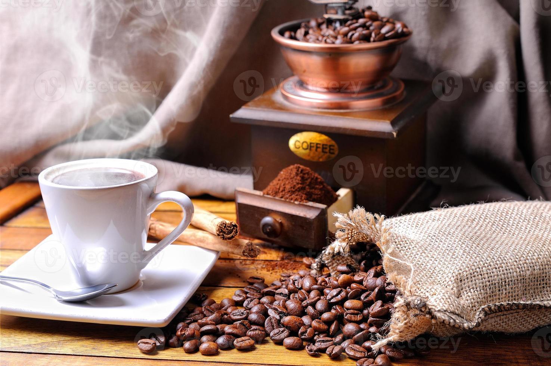 composição com uma xícara de café, feijão e moedor de café foto